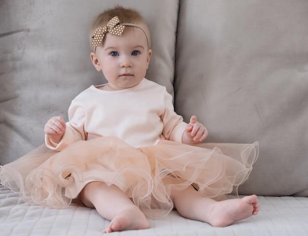 Nettes lustiges kaukasisches blondes baby, das auf der oberfläche der beige weichen sofakissen in der schwarzen kleidung, der braunen schleife sitzt und festliches kleid trägt