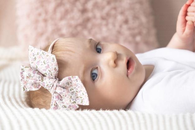 Nettes lustiges kaukasisches blondes baby rosa bogen auf kopf blick auf kamera auf dem bett auf der oberfläche von dekorativen kissen