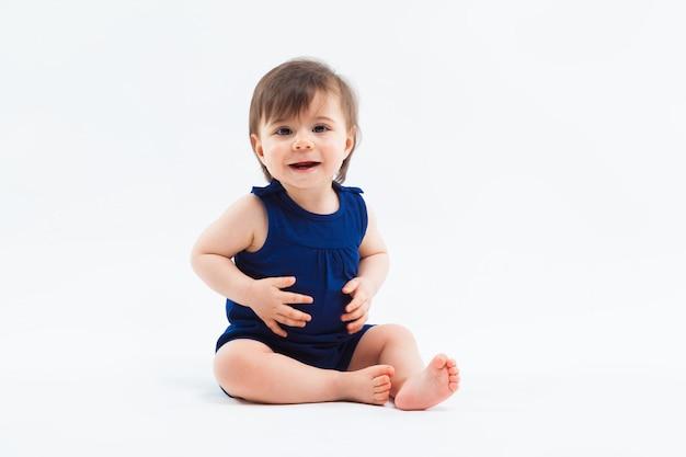 Nettes lustiges kleines lächelndes mädchen, das im studio aufwirft auf weißem hintergrund sitzt