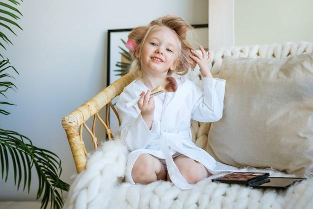 Nettes lustiges kleines mädchen mit lockenwicklern auf ihrem kopf, der in einem stuhl sitzt, der ihr make-up tut
