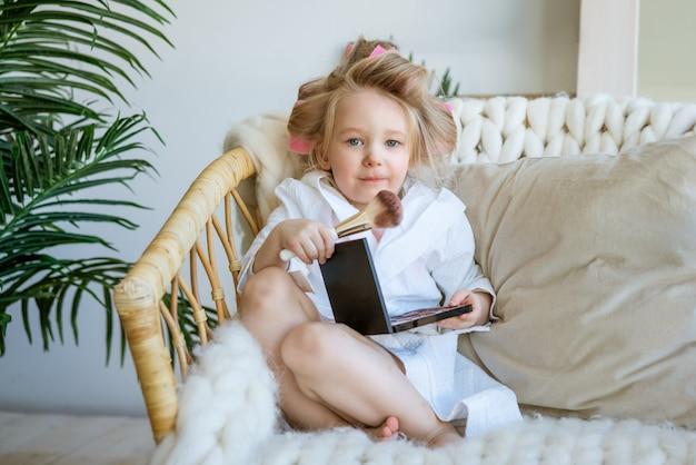 Nettes lustiges kleines mädchen mit lockenwicklern auf ihrem kopf sitzt auf einem stuhl und macht ihr make-up mit einem pinsel
