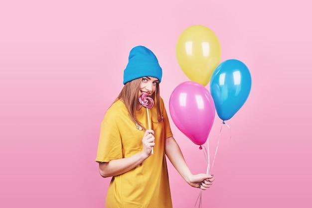 Nettes lustiges mädchen im porträt der blauen kappe hält bunte luftballons der luft und lutscher, die auf rosa hintergrund lächeln. schönes multikulturelles kaukasisches mädchen, das glücklich lächelt.