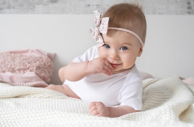Nettes lustiges nachdenkliches kaukasisches blondes baby mit rosa bogen auf kopf liegend ob bettputting finger in den mund