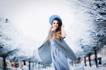 Nettes Mädchen im hellen Sommerkleid, -strickjacke und -hut geht entlang die Parkgasse
