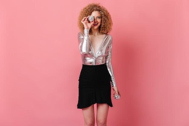 Nettes mädchen bedeckt ihr gesicht mit kleiner discokugel. schuss der stilvollen dame im silberglänzenden oberteil und im schwarzen baumwollrock auf rosa raum.