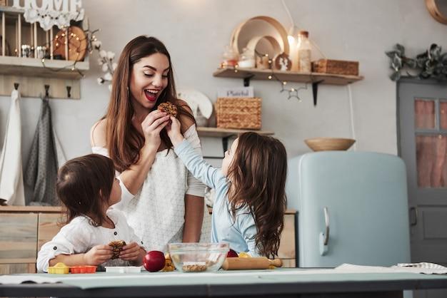 Nettes mädchen beschließt zu teilen. mama ist glücklich. junge schöne frau gibt die kekse, während sie mit spielzeug am tisch sitzen.