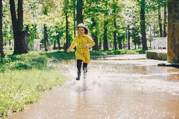 Nettes mädchen, das an einem regnerischen tag plaiyng ist