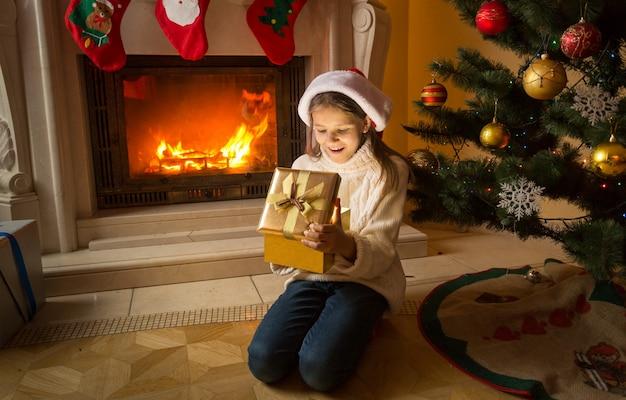 Nettes mädchen, das auf dem boden am kamin sitzt und weihnachtsgeschenk in goldener schachtel erhält