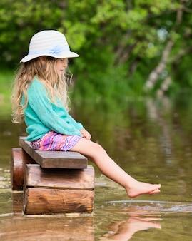 Nettes mädchen, das auf der bank sitzt