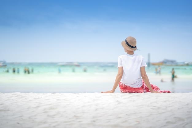 Nettes mädchen, das auf weißem sand für entspannende zeit im sommer auf blauem himmel sitzt