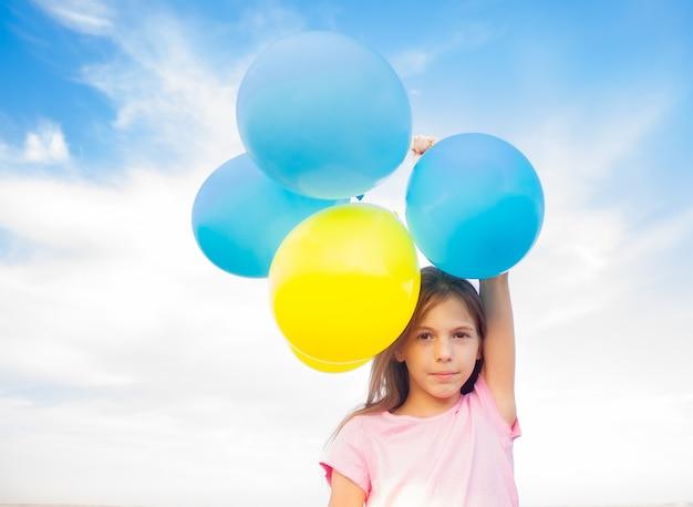 Nettes mädchen, das ballons von blauen und gelben farben in ihren händen hält holding