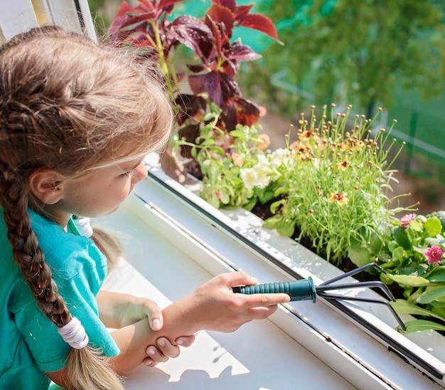 Nettes mädchen, das bei der pflege von hauspflanzen auf dem balkonfensterpflanzen-elternkonzept hilft