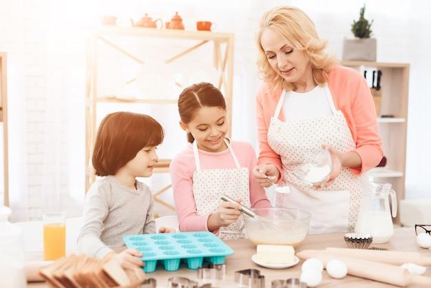 Nettes mädchen, das bestandteile in schüssel auf küche mischt