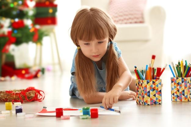 Nettes mädchen, das bild für weihnachten auf dem boden zu hause malt