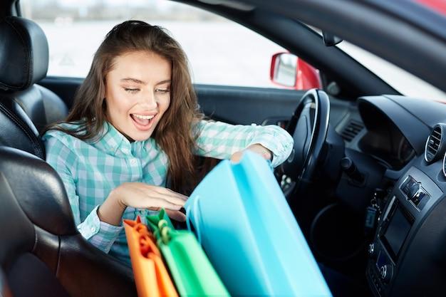 Nettes mädchen, das blaues hemd trägt, das im neuen auto sitzt, im verkehr steckt, porträt, neues auto kauft, fahrerin, einkaufstaschen auf einem sitz, einkaufen, neue sachen betrachtet.