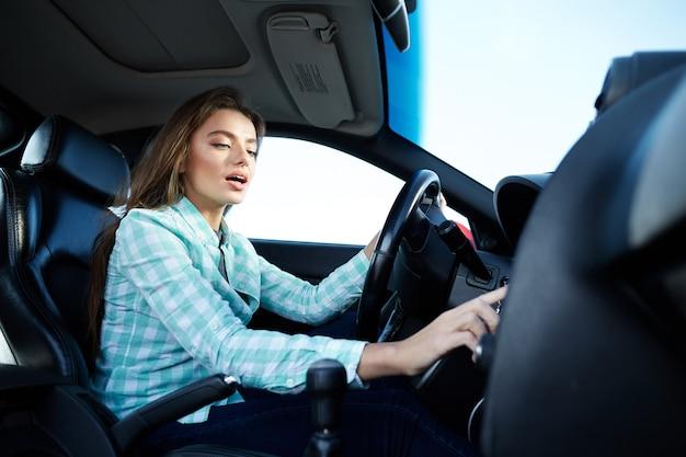 Nettes mädchen, das blaues hemd trägt, das im neuen automobil sitzt, glücklich, im verkehr stecken bleibt, musik hört, knopf drückt, fahrstunden.