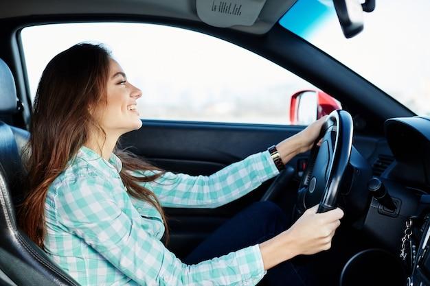 Nettes mädchen, das blaues hemd trägt, das im neuen automobil sitzt, glücklich, im verkehr stecken bleibt, musik hört, porträt.