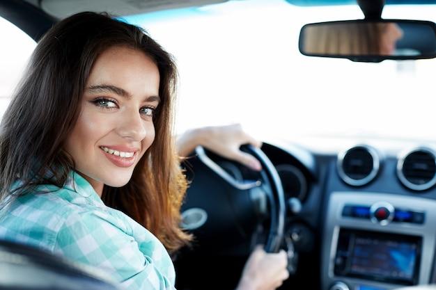 Nettes mädchen, das blaues hemd trägt, das im neuen automobil sitzt, im verkehr, im porträt feststeckt, neues auto, fahrerin kauft, lächelt und kamera betrachtet.