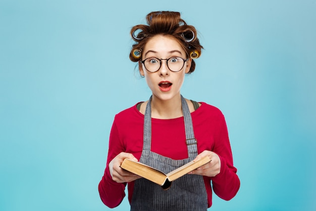Nettes mädchen, das brille und lockenwickler trägt, sieht beim lesen überrascht aus