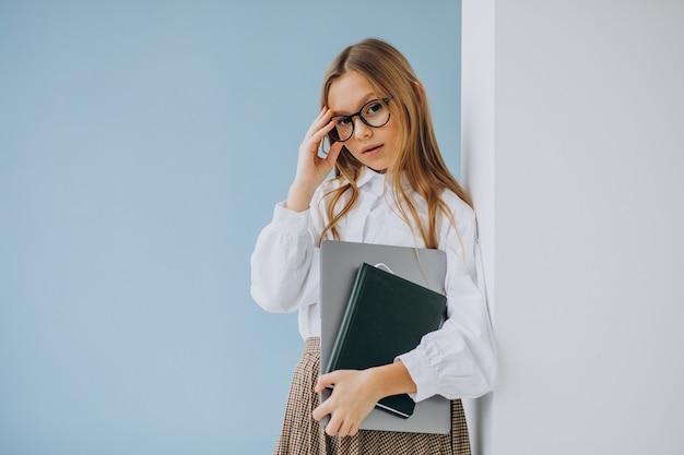 Nettes mädchen, das buch und laptop im büro hält