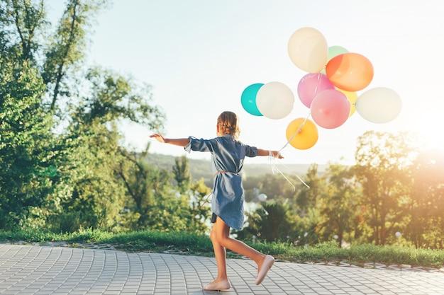 Nettes mädchen, das bunte luftballons im stadtpark hält