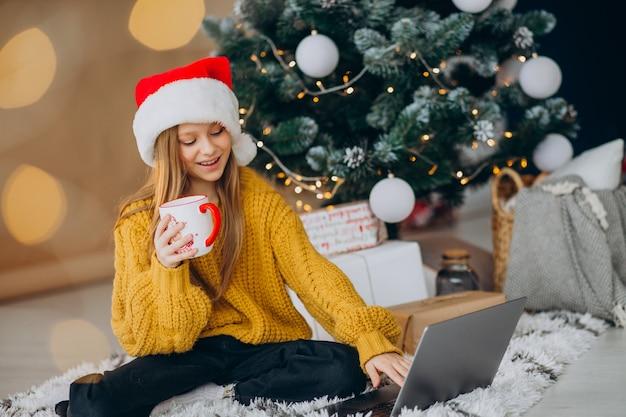 Nettes mädchen, das computer durch weihnachtsbaum benutzt