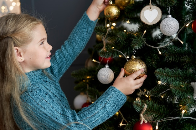 Nettes mädchen, das dekorationen am weihnachtsbaum hängt