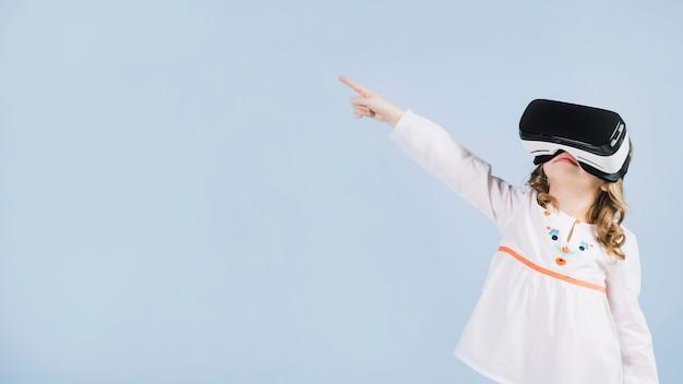 Nettes mädchen, das den virtuellen kopfhörer zeigt ihren finger auf etwas verwendet