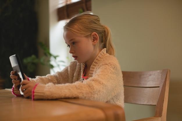 Nettes mädchen, das digitales tablett im wohnzimmer verwendet
