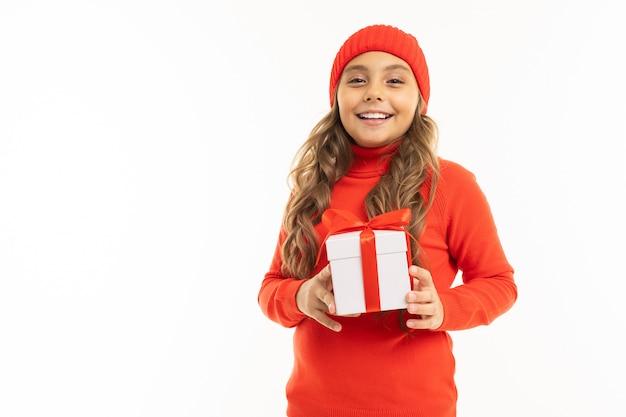 Nettes mädchen, das eine geschenkbox auf weißer wand hält