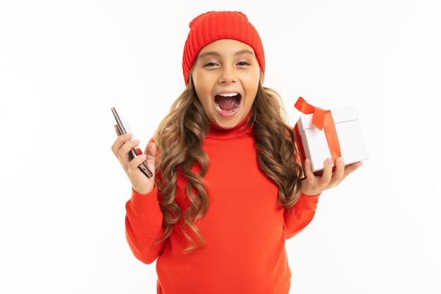 Nettes mädchen, das eine geschenkbox und ein telefon hält und schreit, dass sie einen preis gewann
