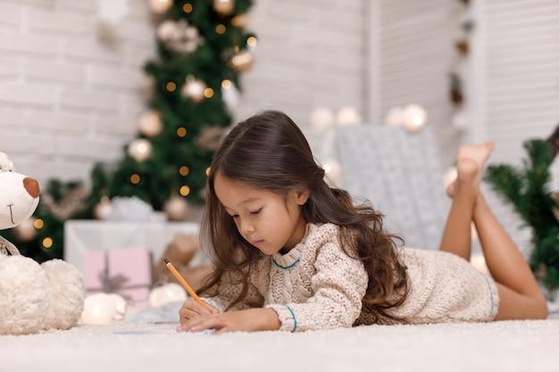 Nettes mädchen, das einen brief an den weihnachtsmann zu hause schreibt