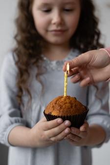 Nettes mädchen, das einen cupcake in ihren händen mit einer kerze hält