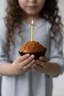 Nettes mädchen, das einen feierlichen cupcake hält.