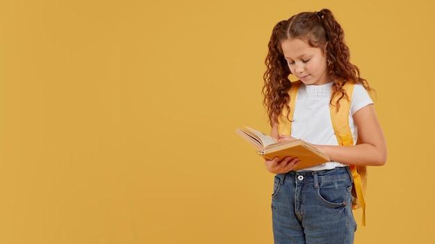 Nettes mädchen, das gelben rucksack trägt und liest