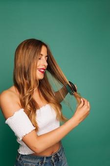 Nettes mädchen, das ihre haare putzt und lacht