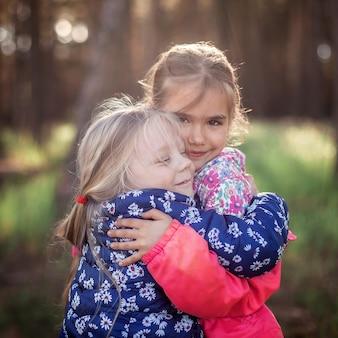 Nettes mädchen, das ihre kleine schwester mit liebe und zärtlichkeit während ihres gehens im wald im herbst, nationalen umarmungs- und freundschaftstag, lässiger lebensstil, im freien umarmt