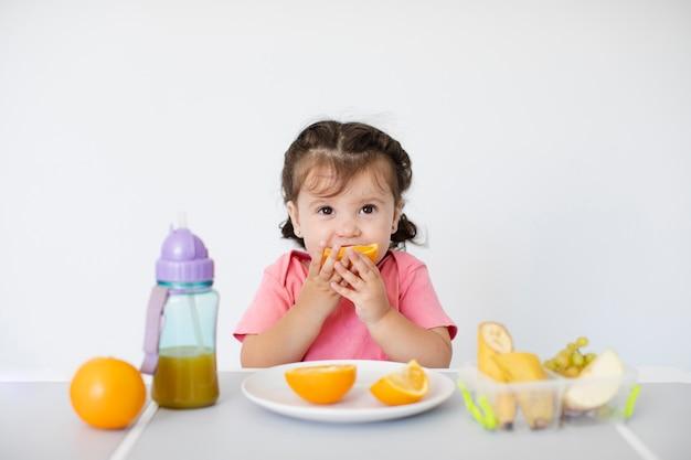 Nettes mädchen, das ihre orangen sitzt und genießt
