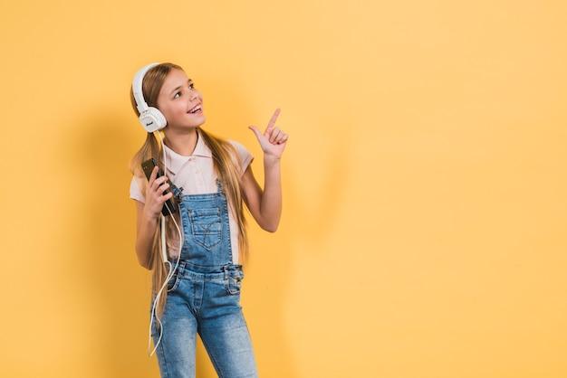 Nettes mädchen, das in der hand bewegliche hörende musik durch den kopfhörer hält, der finger aufwärts gegen gelben hintergrund zeigt