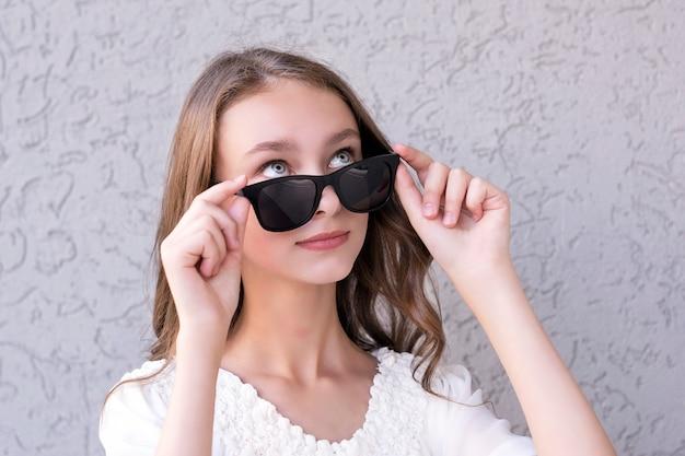 Nettes mädchen, das in der sonnenbrille aufwirft
