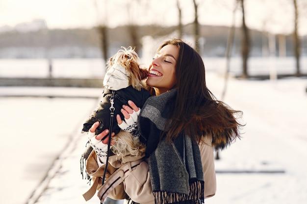 Nettes mädchen, das in einem winterpark mit ihrem hund geht