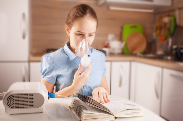 Nettes mädchen, das inhalation macht und buch in der küche liest