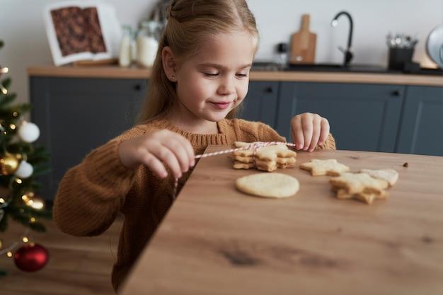 Nettes mädchen, das kekse für weihnachtsmann packt