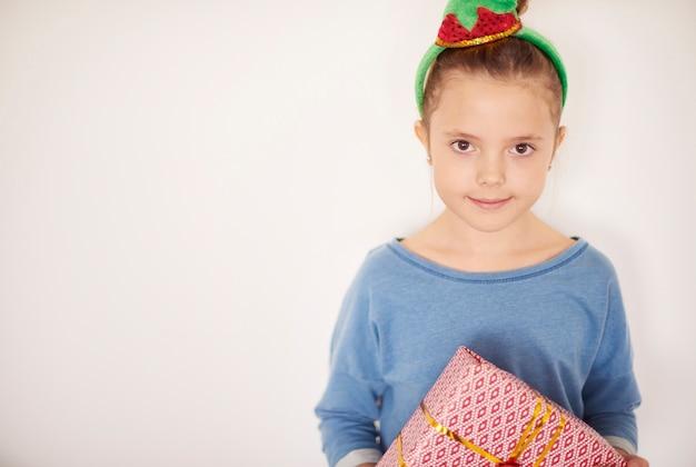 Nettes mädchen, das kostümelfen mit weihnachtsgeschenk trägt