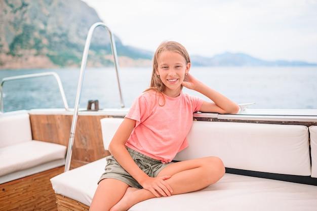 Nettes mädchen, das lächelt und das segeln auf boot im offenen meer genießt
