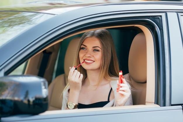 Nettes mädchen, das lippenstift in einem auto anwendet