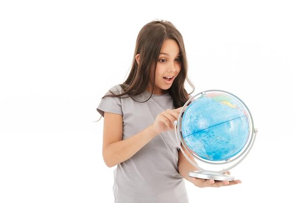 Nettes mädchen, das lokalisiert hält globus hält.