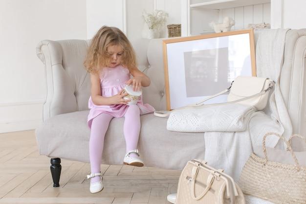 Nettes mädchen, das mit glas auf elegantem sofa spielt