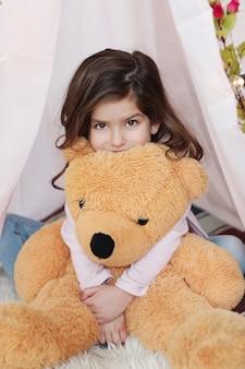 Nettes mädchen, das mit großem teddybär aufwirft