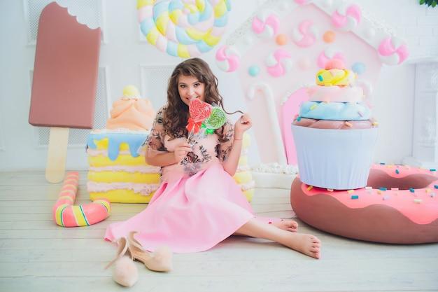 Nettes mädchen, das mit rosa donuts aufwirft, herumalbern, dessert, schlechtes essen, schaut in das loch im donut, hält donuts durch die augen Premium Fotos